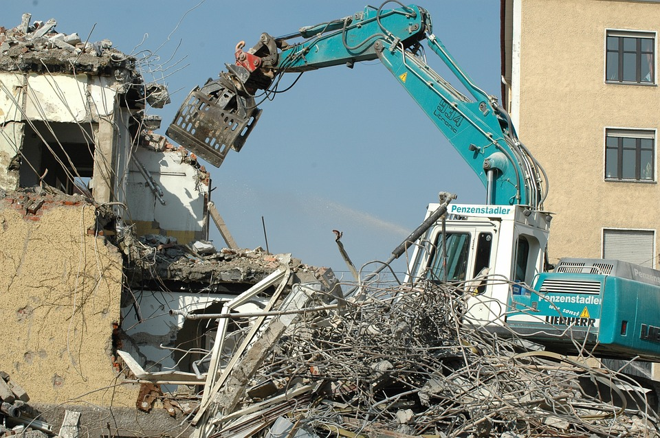 excavator with claw attachment demolishing a building