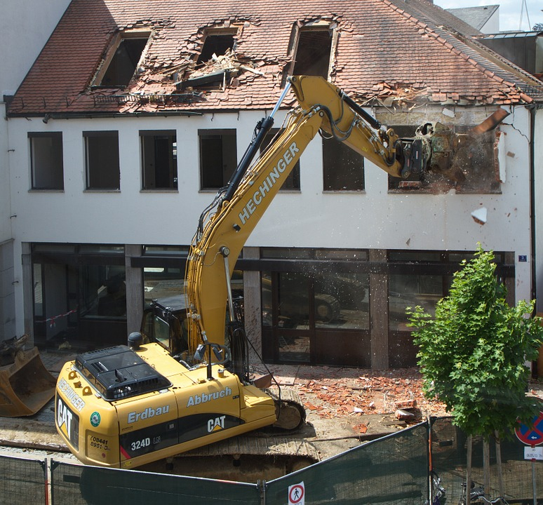 excavator demolshing the upper level of a house