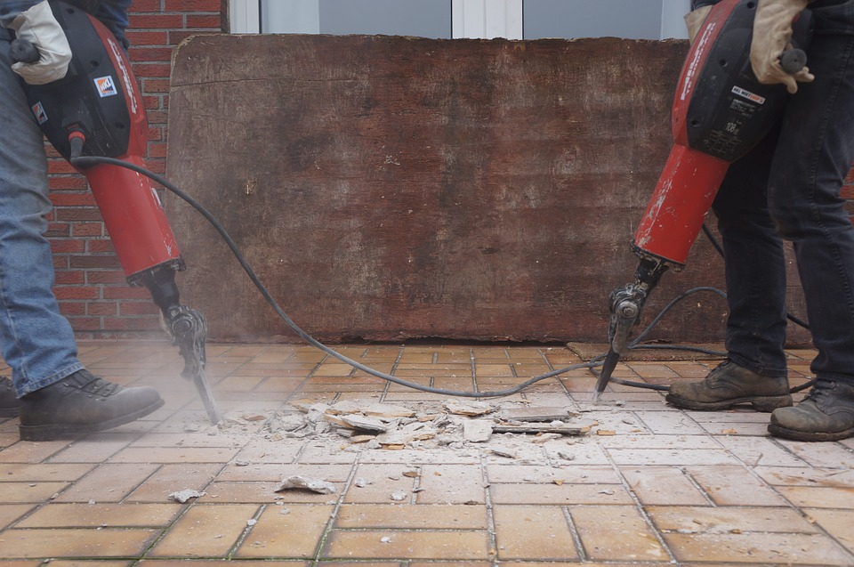 workers using jackhammers to break up and remove floor tiles