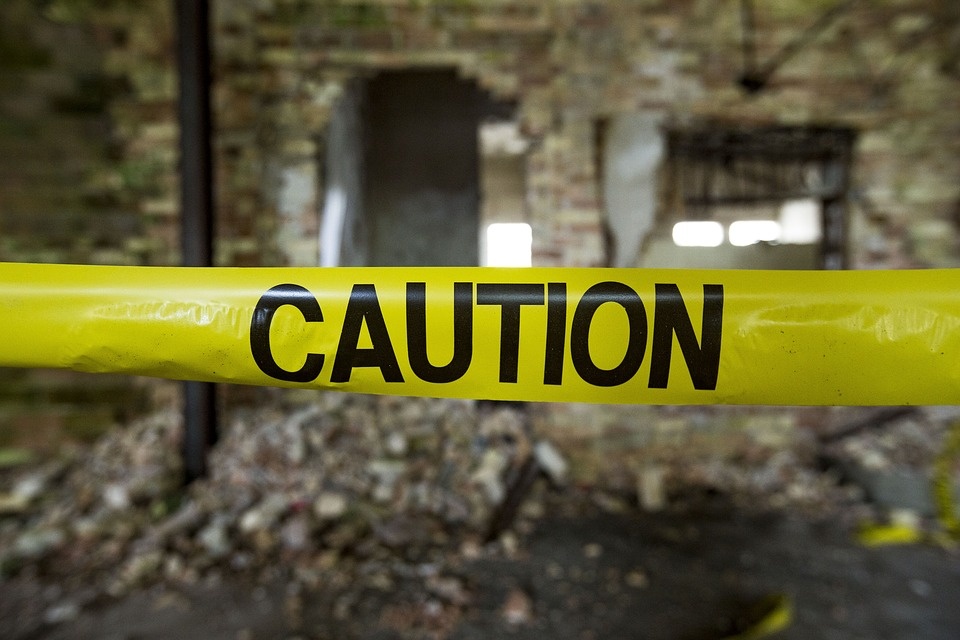 caution tape in front of a demolition site